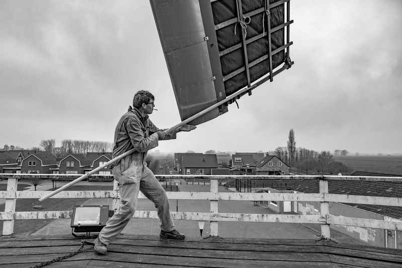 The local miller is giving the windmill a swing Blackandwhite Composition Holland Industrial Miller Netherlands Occupation Outdoors Perspective Portrait Rural Safety Selective Focus View Windmill Wood - Material Working Www.benjaminvanderspek.com Zeeland  Learn & Shoot: Working To A Brief Natural Light Portrait Adventure Club Monochrome Photography Uniqueness Wind Mill