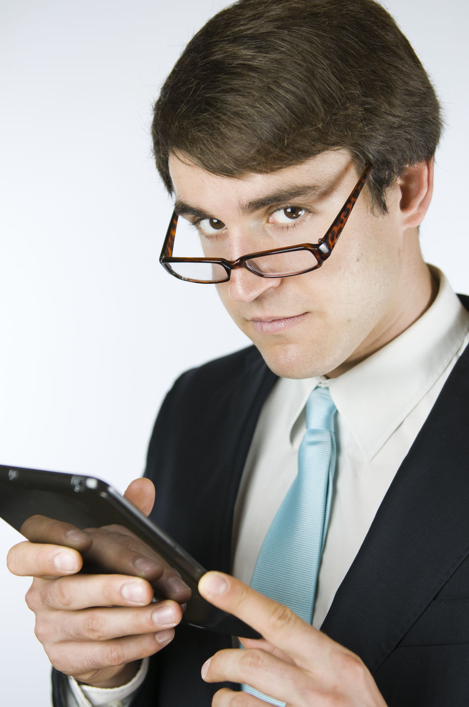 View of the upper body of a young man in the suit a tablet in the hands hatend with serious look over the edge of the glasses in the direction of camera looking. Casual Clothing Glases Handsome Holding Indoors  IPad Mini Look Over The Glasses Looking Looking At Camera Man Person Professional Occupation Sceptical Sceptical Look Studio Shot Tie Waist Up White Background Young Adult