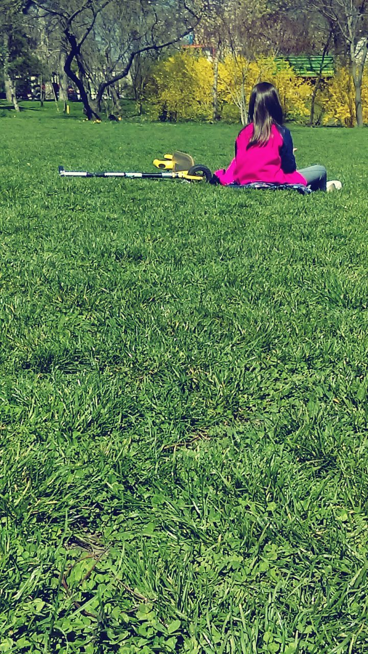 grass, green color, one person, full length, pink color, sitting, nature, rear view, outdoors, tree, day, leisure activity, one woman only, real people, only women, women, beauty in nature, flower, young women, young adult, adult, one young woman only, people, adults only