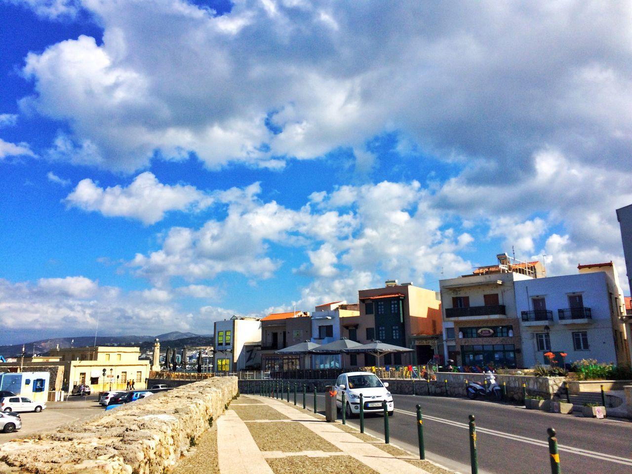architecture, building exterior, cloud - sky, sky, built structure, car, day, outdoors, land vehicle, city, transportation, blue, road, no people, cityscape
