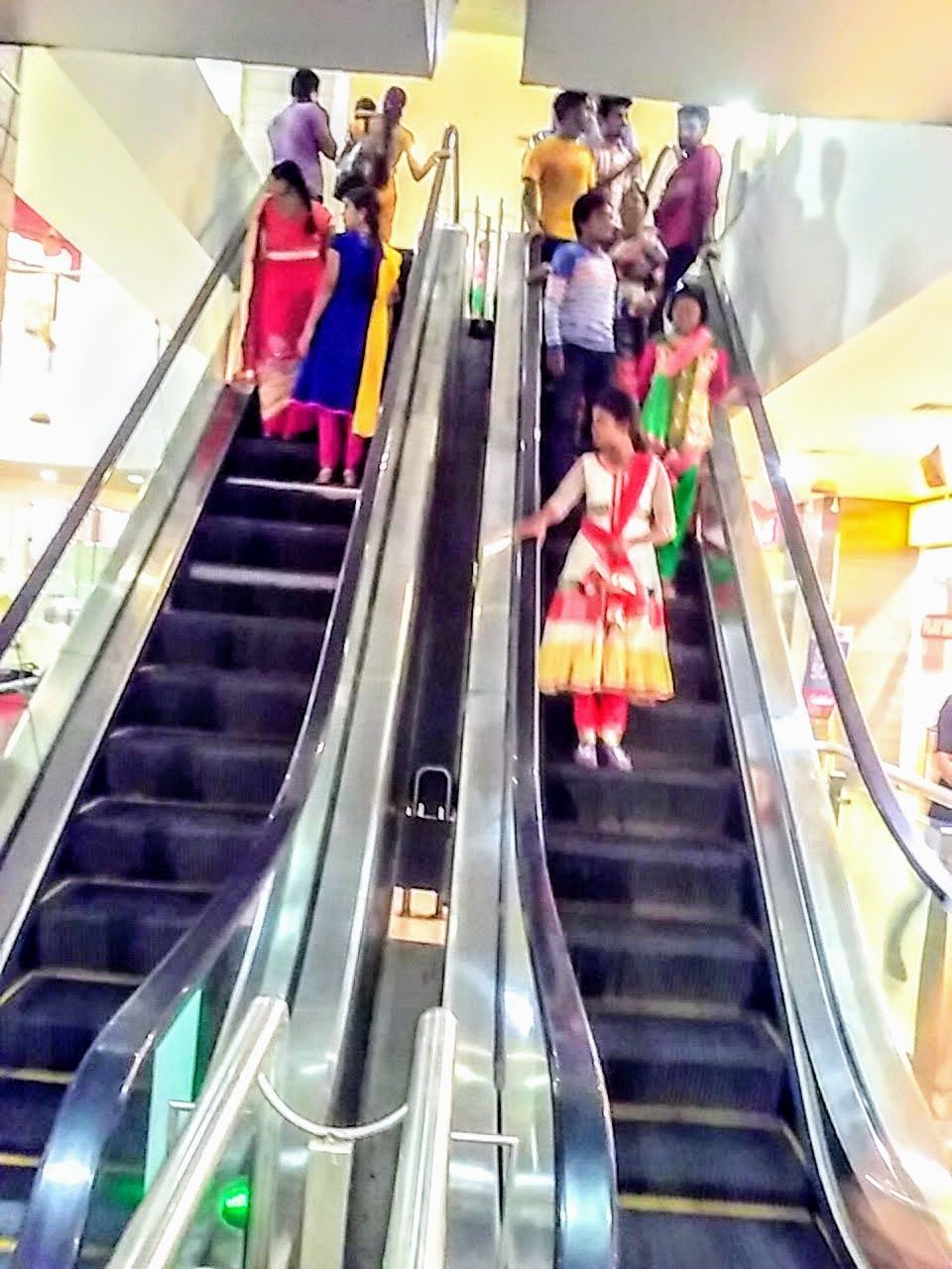escalator, indoors, steps, steps and staircases, staircase, men, high angle view, modern, convenience, lifestyles, real people, leisure activity, women, casual clothing, large group of people, technology, retail, group of people, architecture, futuristic, day, adult, people, adults only