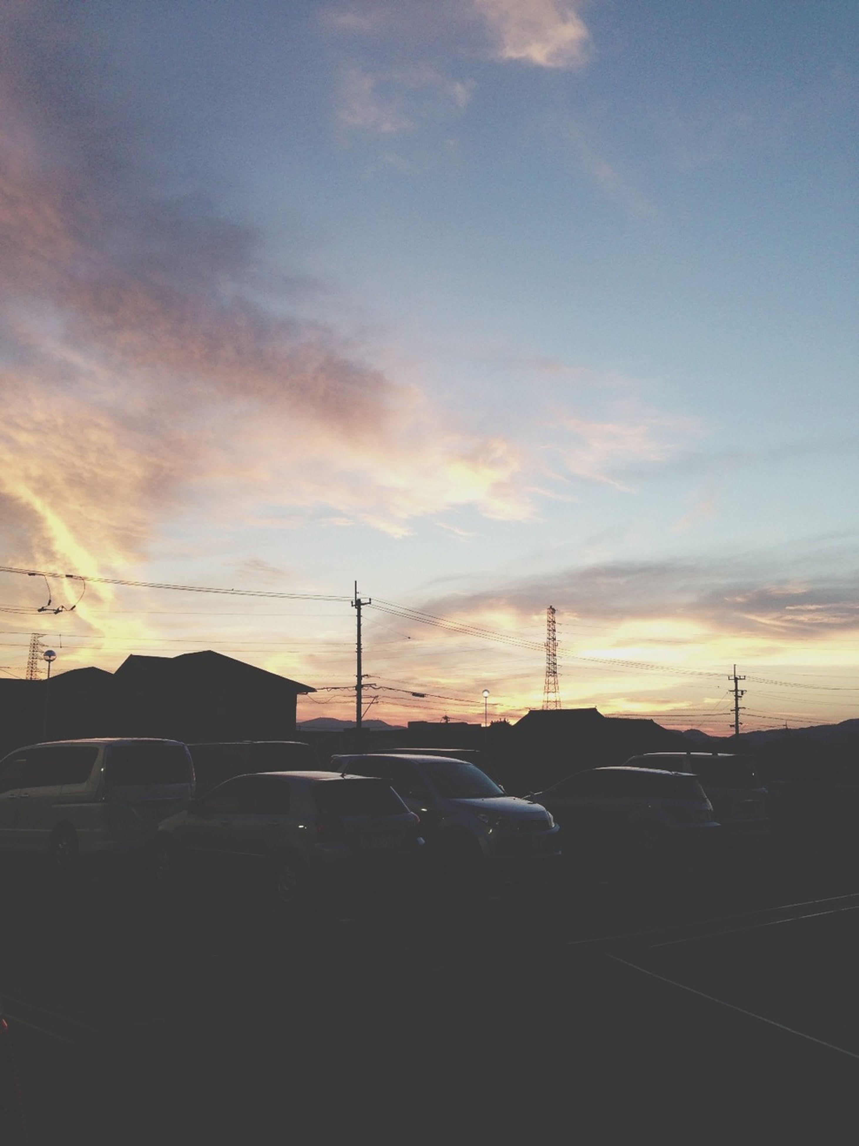 sunset, transportation, car, sky, land vehicle, mode of transport, silhouette, street light, road, cloud - sky, building exterior, electricity pylon, street, built structure, power line, orange color, architecture, cloud, outdoors, city