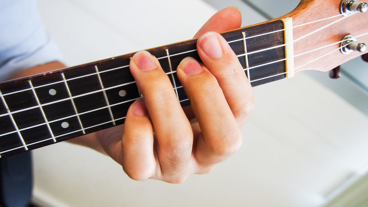 Man playing ukulele chord Chords Classic Close-up Day Fingers Folk Fretboard Guitar Hobbies Human Hand Indoors  Joy Melody Music Musical Instrument One Person Performance Playing Relaxing Song Strings Ukulele Wood