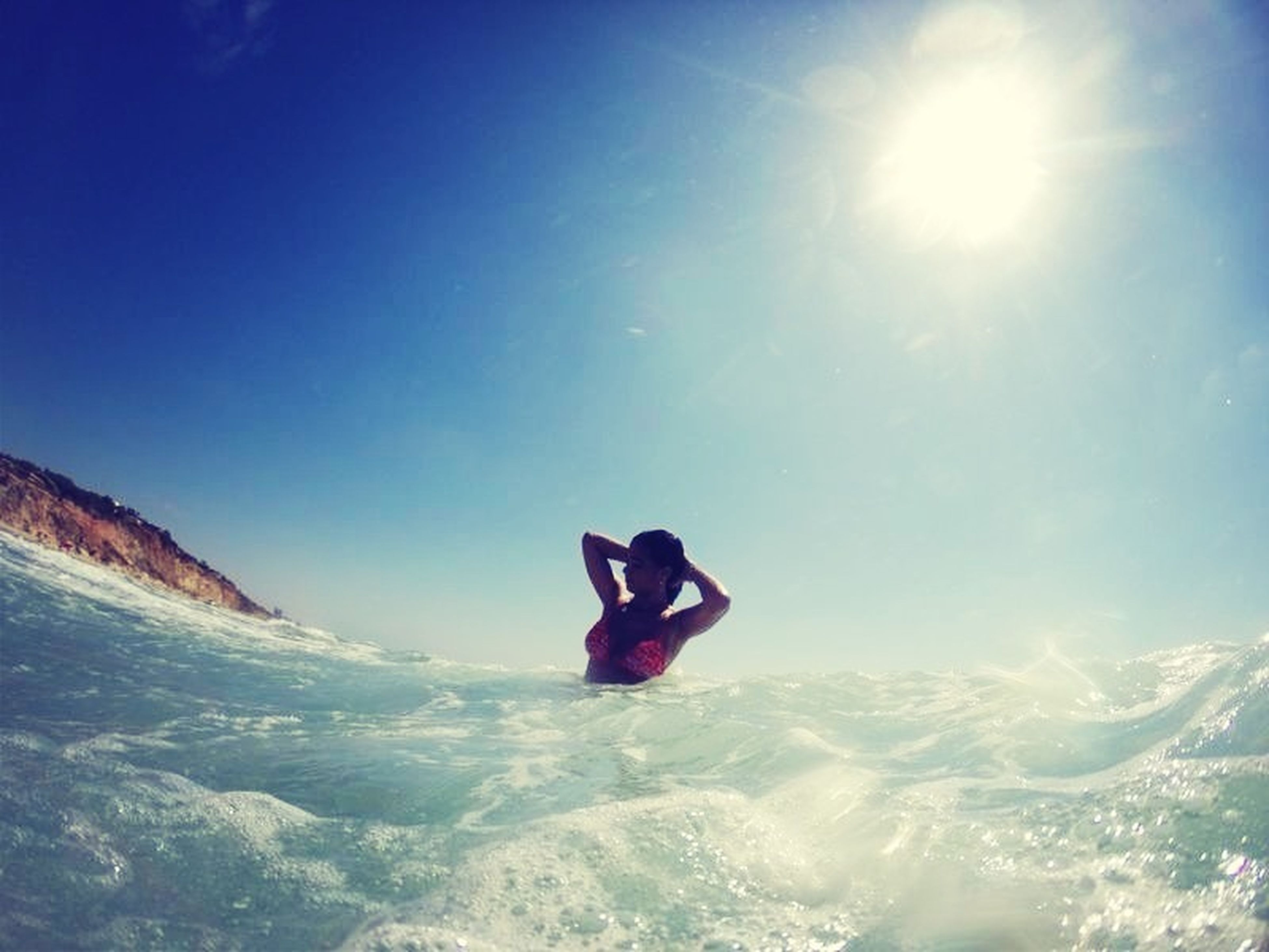 leisure activity, lifestyles, sunlight, blue, water, vacations, sea, extreme sports, adventure, sky, full length, young adult, enjoyment, beauty in nature, nature, sunny, sun, scenics