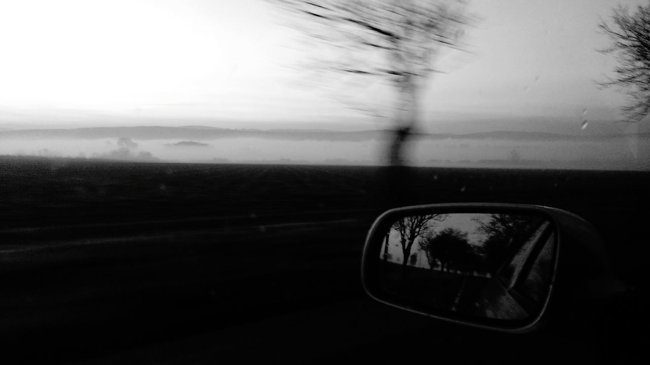 glass - material, window, transportation, car, sky, mode of transport, road, side-view mirror, land vehicle, landscape, windshield, car interior, day, nature, motion, vehicle mirror, no people, car point of view, close-up, indoors, tree