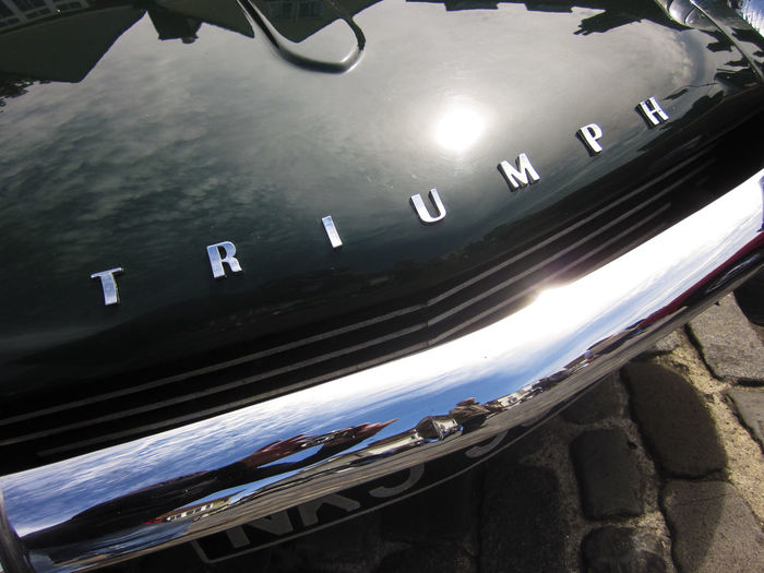 Triumph car front badge 1950s 1960s Blurred Motion British Canal Car Car Front Badge Day Design High Angle View Journey Mode Of Transport On The Move Reflection Stationary Transportation Travel Vivid International Water Window