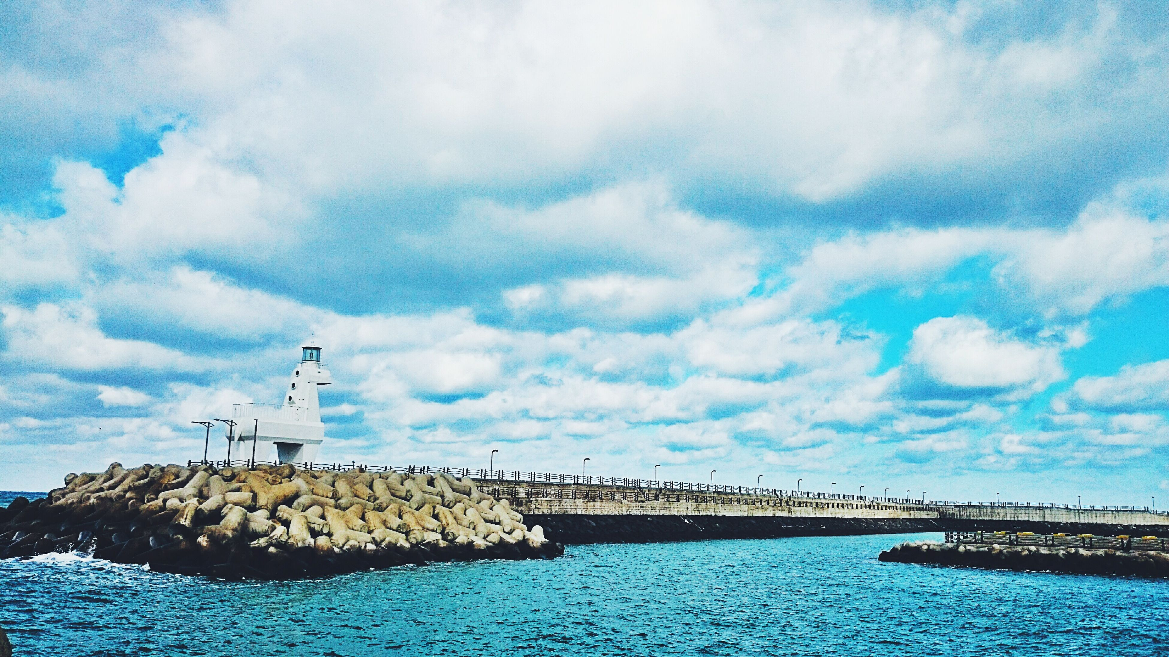 water, lighthouse, sea, built structure, sky, architecture, cloud - sky, waterfront, building exterior, guidance, tranquility, tranquil scene, cloud, blue, scenics, nature, direction, pier, cloudy, beauty in nature