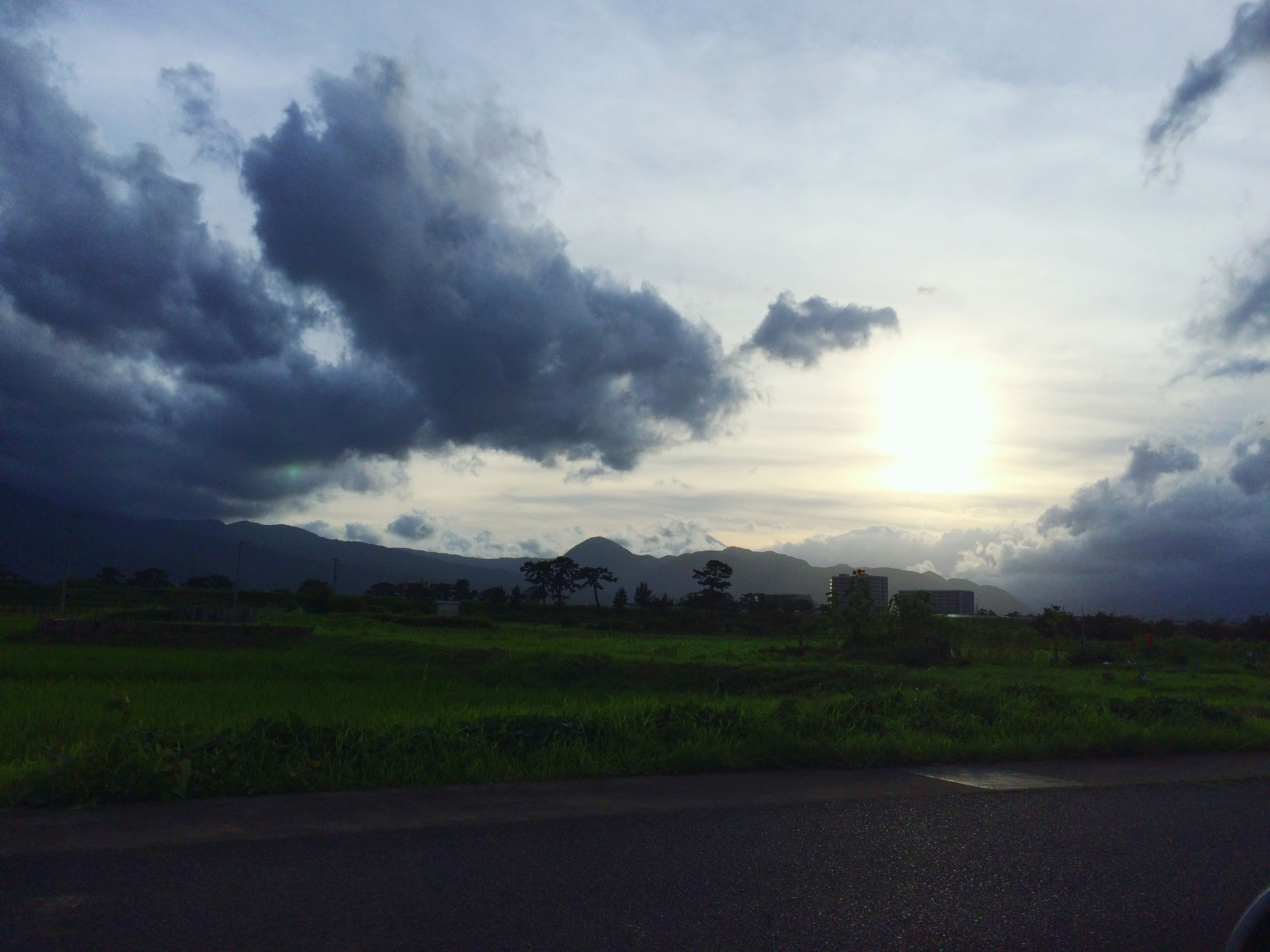 sky, cloud - sky, landscape, tranquil scene, tranquility, sun, scenics, cloudy, beauty in nature, sunbeam, road, nature, sunlight, cloud, field, sunset, mountain, weather, idyllic, grass