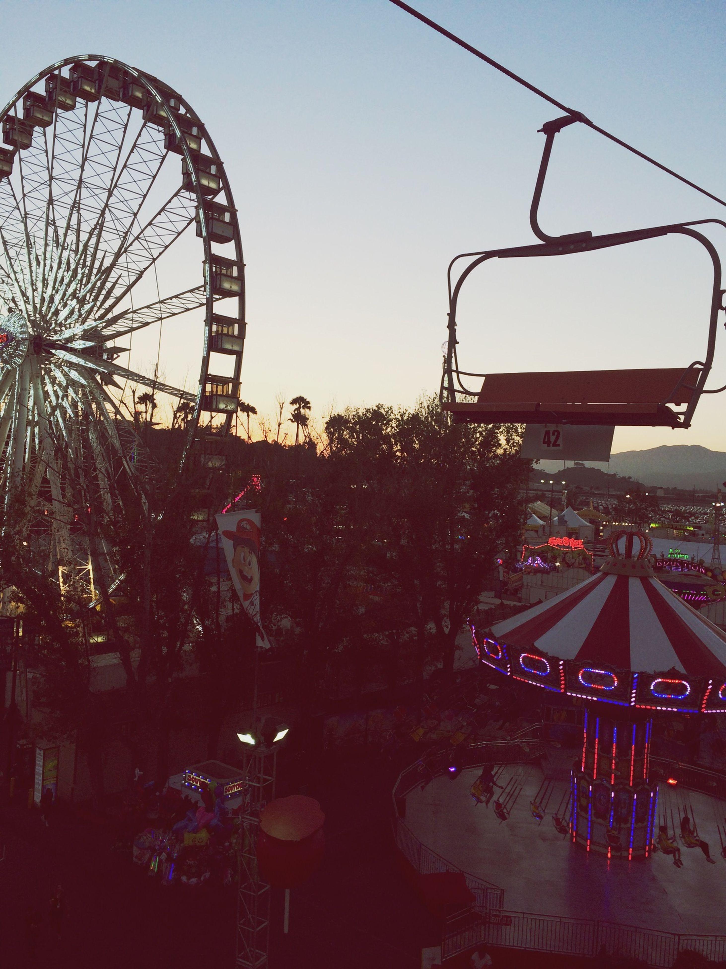 amusement park, ferris wheel, amusement park ride, arts culture and entertainment, sky, clear sky, built structure, architecture, illuminated, tree, building exterior, dusk, outdoors, transportation, incidental people, travel destinations, city, water, low angle view, fun