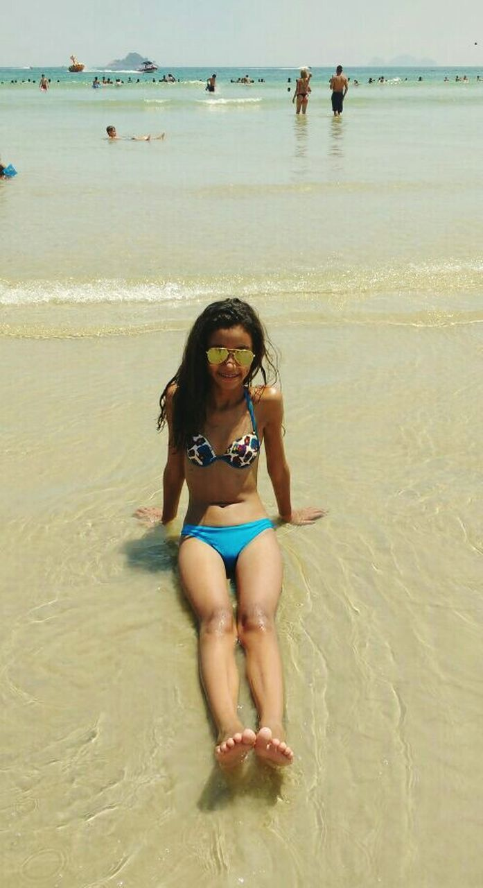 beach, sand, sea, looking at camera, water, real people, portrait, shore, smiling, vacations, leisure activity, bikini, full length, one person, lifestyles, outdoors, happiness, nature, day, beauty in nature, summer, sitting, young adult, young women, scenics, childhood, horizon over water, sky, people, adult