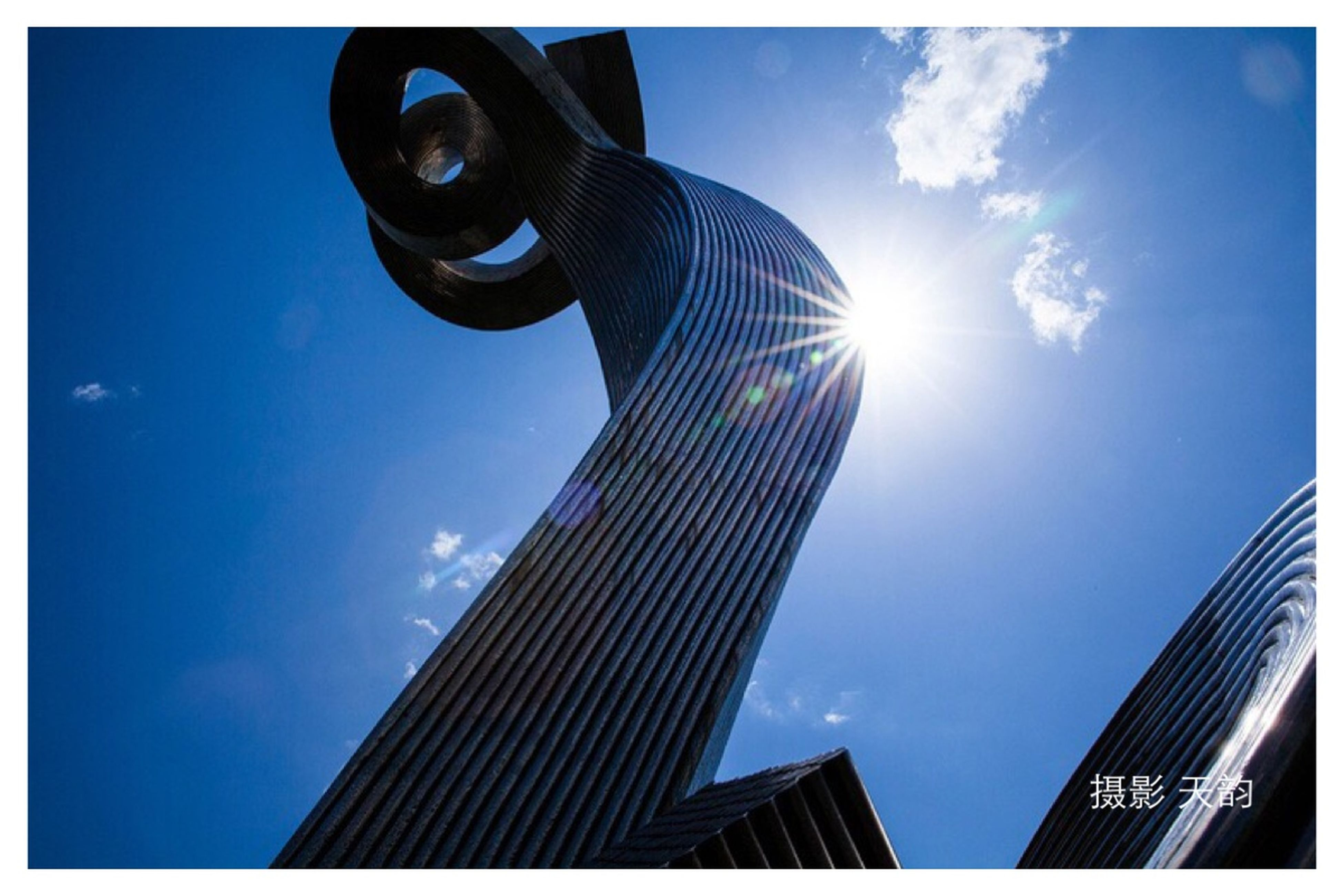 low angle view, architecture, built structure, building exterior, transfer print, sky, blue, auto post production filter, sunlight, cloud, cloud - sky, modern, city, sunbeam, tall - high, street light, building, day, sun, outdoors
