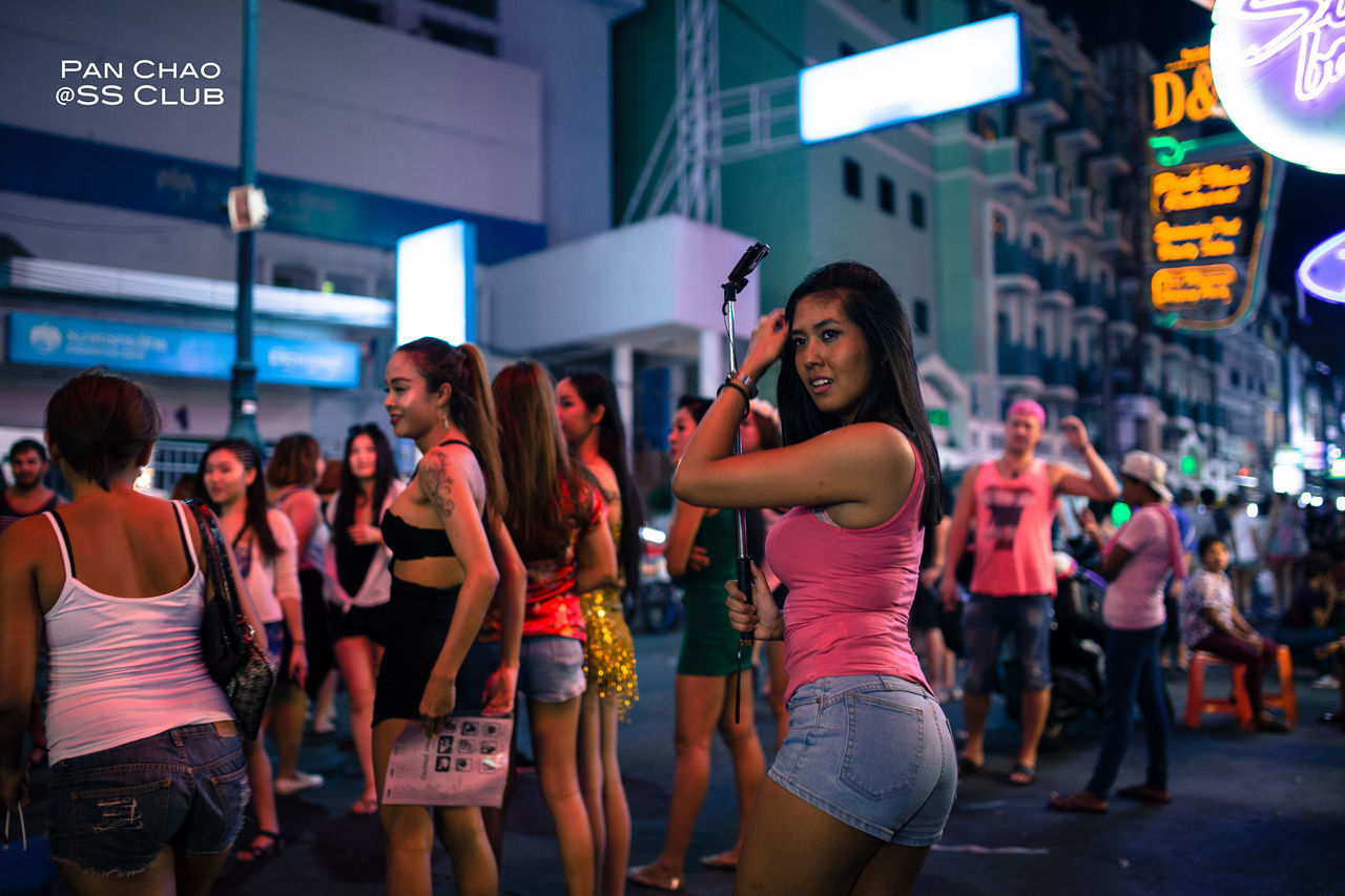 real people, leisure activity, standing, technology, communication, large group of people, women, enjoyment, lifestyles, young adult, young women, photography themes, night, wireless technology, cheerful, architecture, men, illuminated, friendship, outdoors, city, adult, people