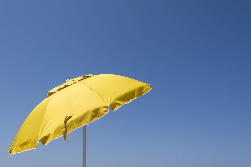 Yellow sun umbrella against the blue sky Copy Space Greek Holiday Hot Isolated Mediterranean  Pacific Summertime Sunny Travel Vacations Backgrounds Blue Sky Island Open Outdoors Parasol Protection Summer Sun Sunbathing Tourism Umbrella Vibrant Color Yellow