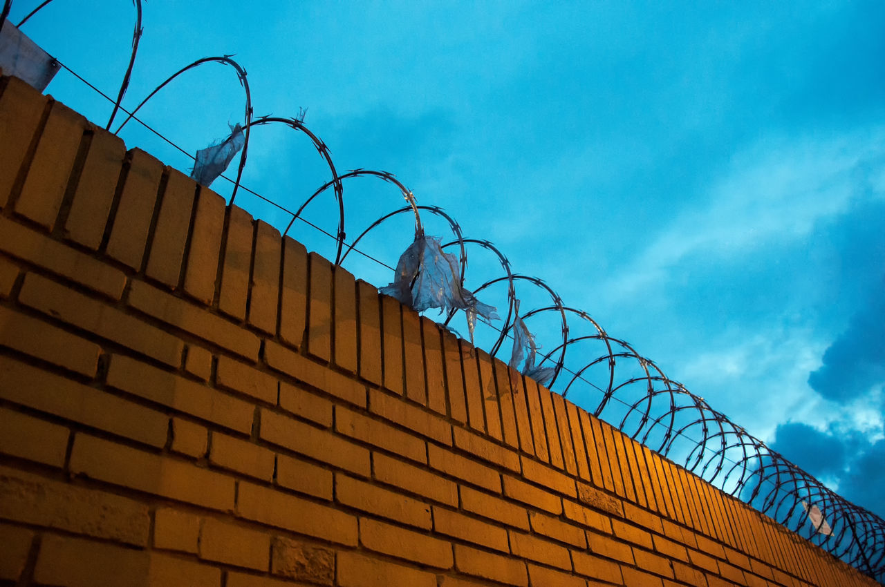A yellow brick fence with barbed wire on top of it Barbed Barbwire Barrier Beautiful Blue Bogotá Capital City Closed Colombia Danger Dangerous Fence Forbidden Freedom Guard Limit Night Prevent Protection Sky South America Tourism Travel Wall