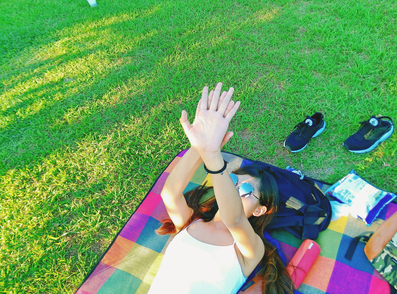 grass, high angle view, real people, one person, day, outdoors, leisure activity, field, lifestyles, lying down, childhood, green color, girls, relaxation, summer, vacations, nature, young adult, human hand, people