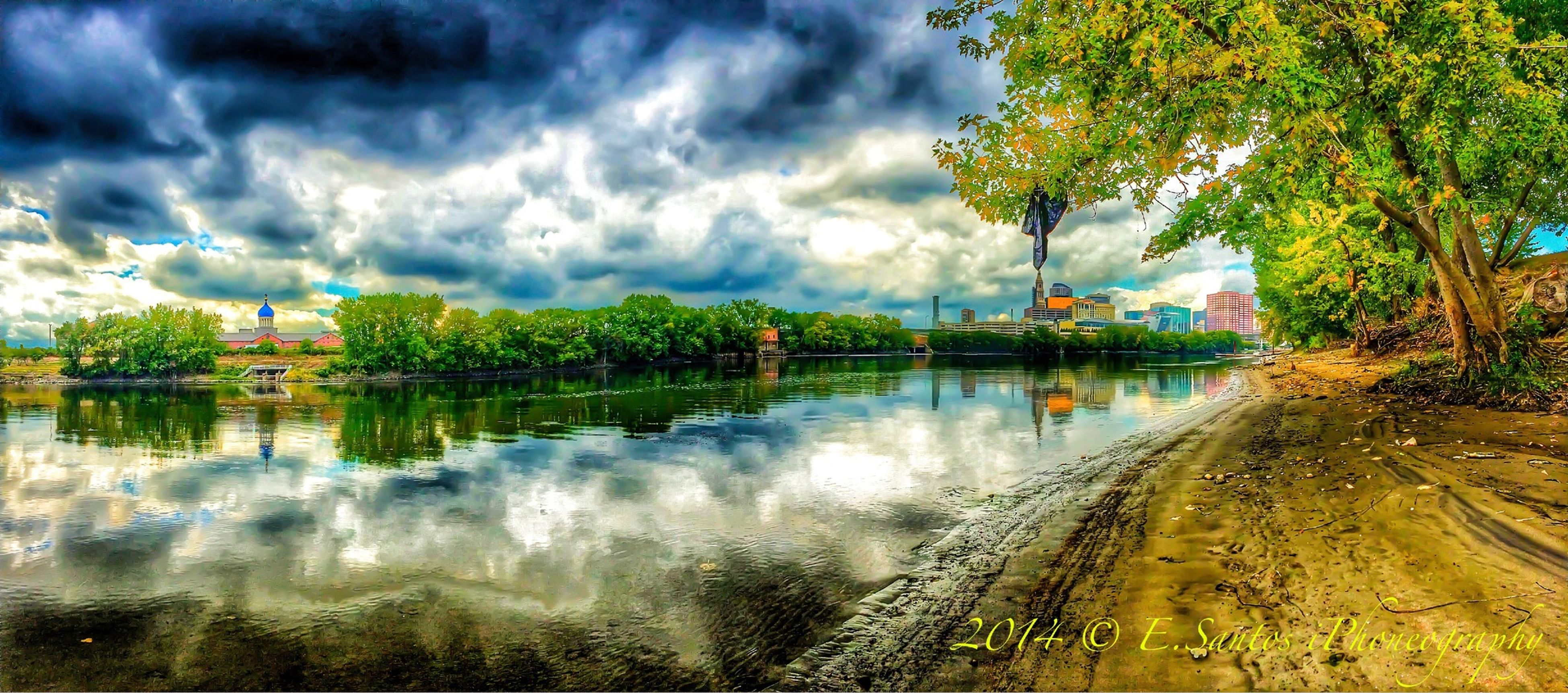 sky, water, cloud - sky, cloudy, tree, built structure, architecture, transportation, reflection, building exterior, weather, cloud, river, nature, waterfront, overcast, road, outdoors, beauty in nature, tranquility