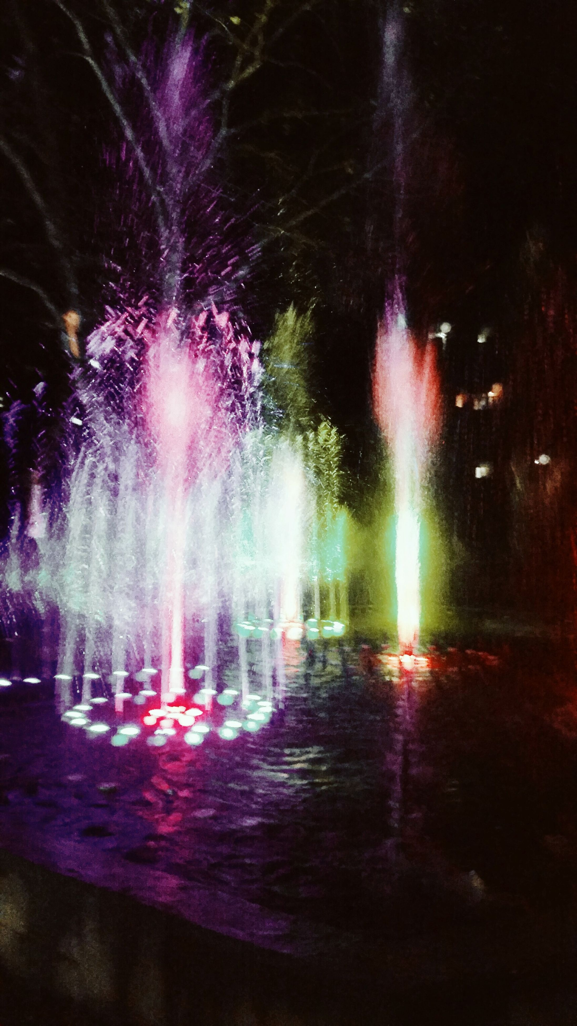 night, illuminated, long exposure, motion, glowing, water, reflection, multi colored, blurred motion, waterfront, tree, firework display, celebration, fountain, outdoors, light - natural phenomenon, no people, exploding, sky, light