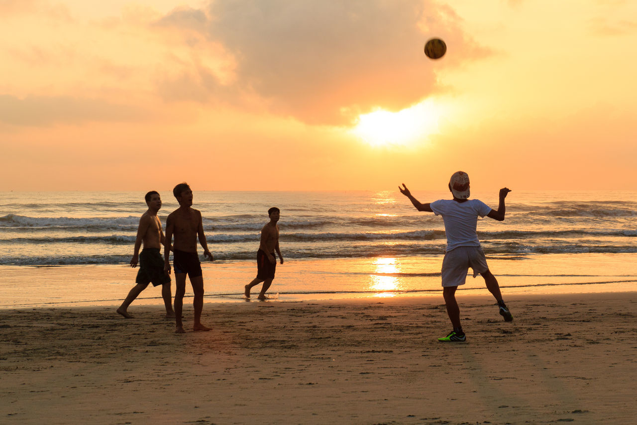 beach, sunset, sand, sea, shore, sky, horizon over water, orange color, sport, leisure activity, real people, nature, silhouette, water, playing, ball, men, scenics, lifestyles, enjoyment, outdoors, mid-air, sun, exercising, cloud - sky, activity, beauty in nature, healthy lifestyle, vacations, togetherness, standing, wave, full length, beach volleyball, sportsman, day, adult, people