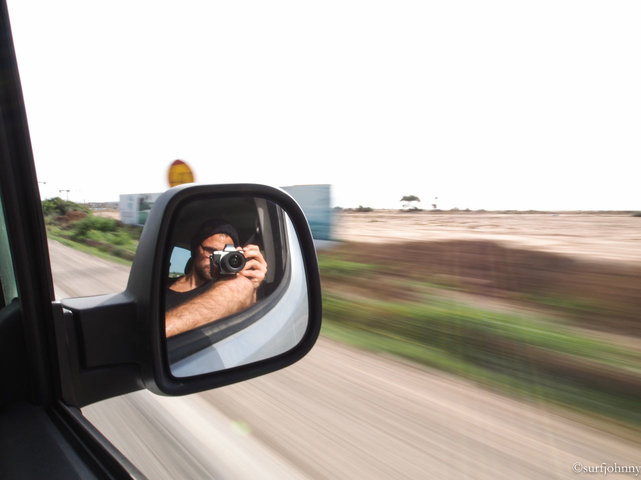real people, car, transportation, mode of transport, land vehicle, one person, lifestyles, sunglasses, young adult, side-view mirror, leisure activity, young women, headshot, day, holding, photographing, technology, clear sky, men, outdoors, nature, sky, human hand, people