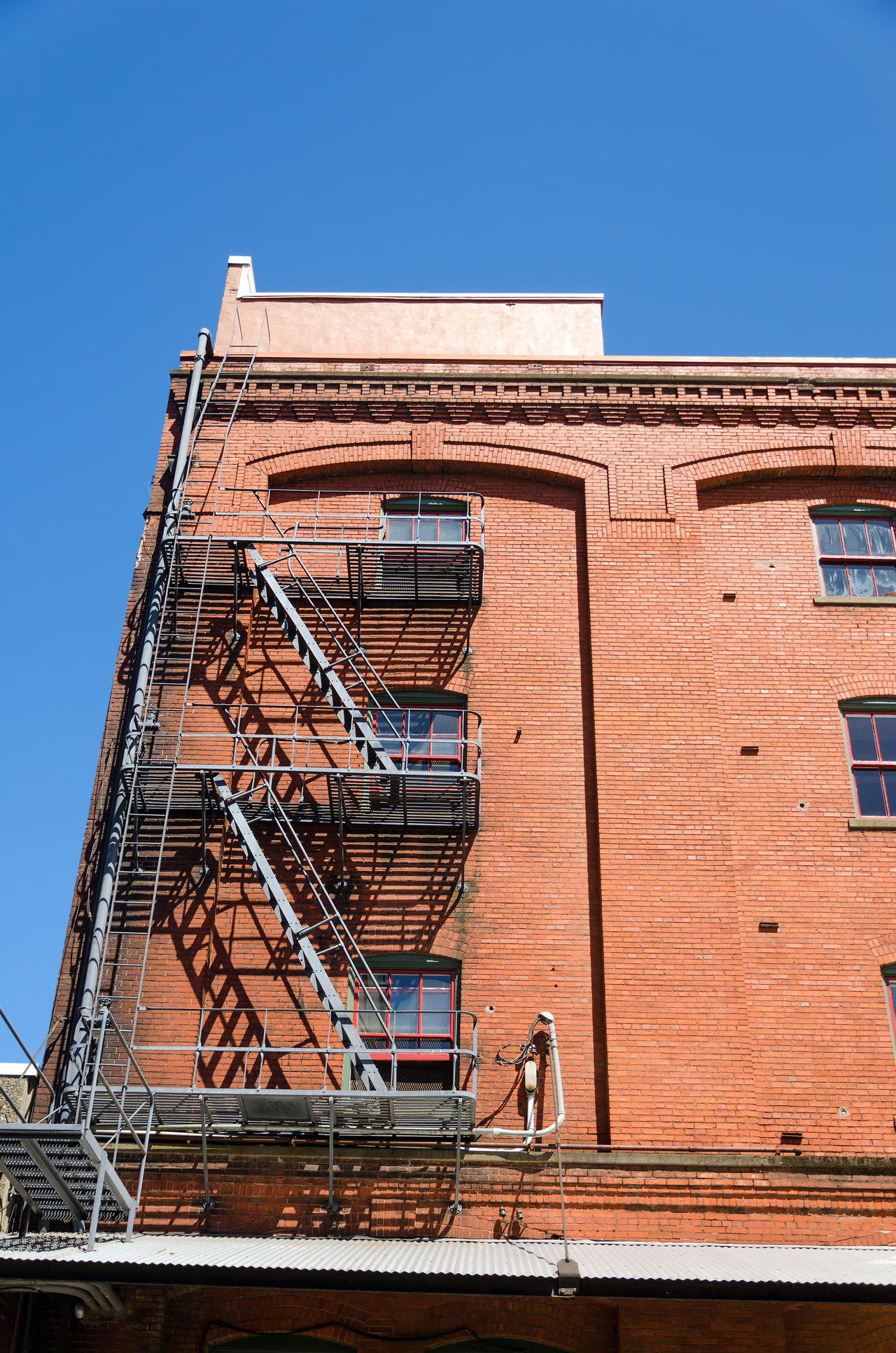 Fire escape running down the side of a red brick building in Portland, Oregon America Aparment Architecture Building Business Center City Cityscape Downtown Exterior Landmark Metropolis Modern Northwest Oregon Outodoors Pacific Portland Skyline Structure Tourism United States Urban USA View