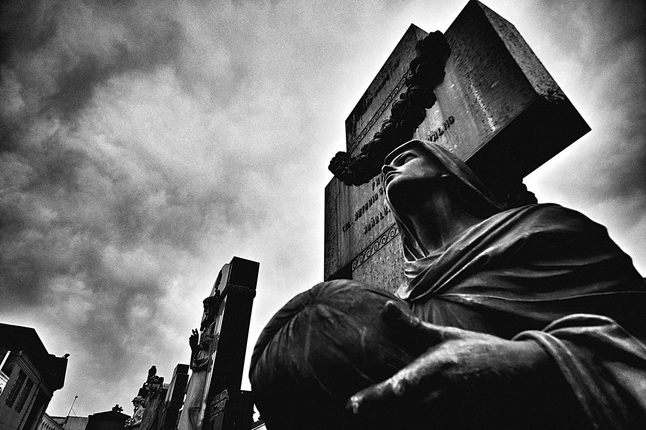 Low Angle View Of Statue And Tombstone Against Cloudy Sky
