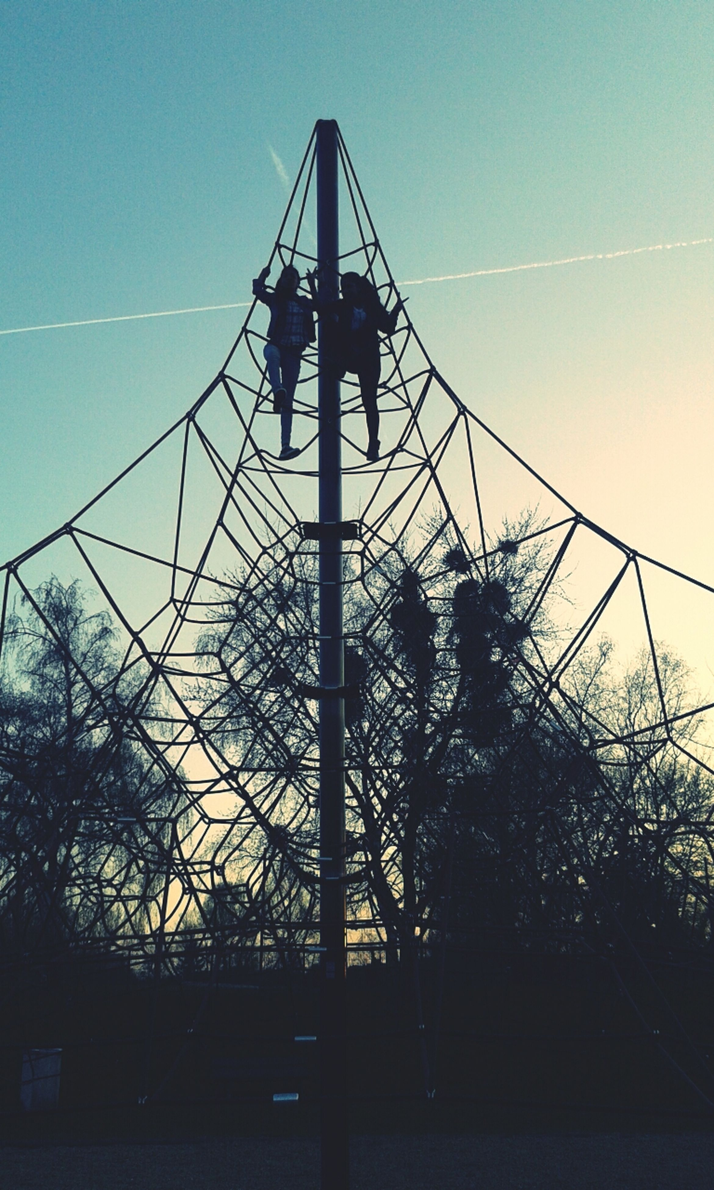 low angle view, connection, clear sky, silhouette, sky, built structure, blue, electricity pylon, tree, metal, technology, electricity, bridge - man made structure, architecture, power line, engineering, dusk, outdoors, sunset, sunlight