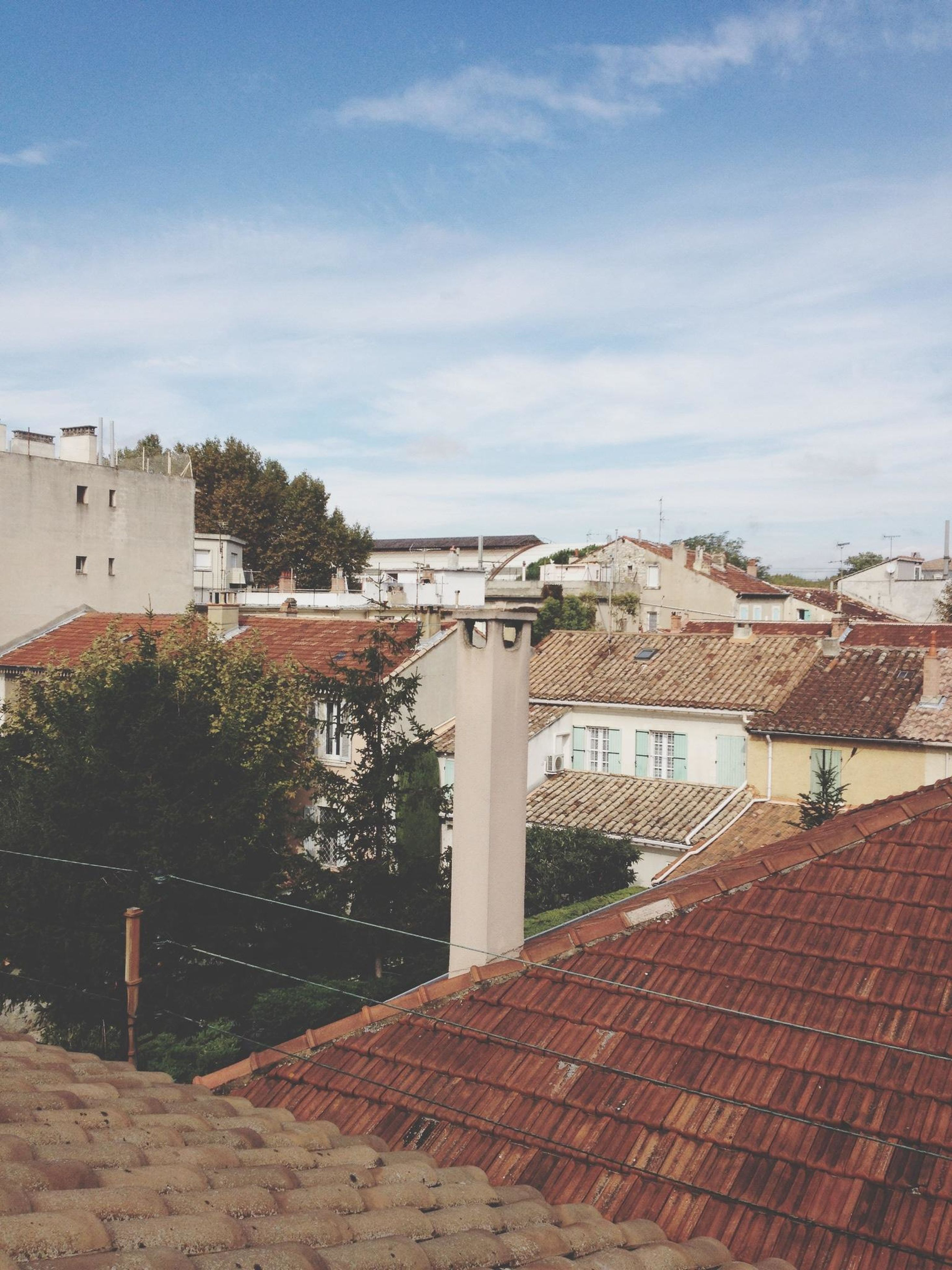 architecture, building exterior, built structure, sky, cloud - sky, roof, house, residential structure, residential building, city, cloud, sunlight, day, outdoors, tree, railing, town, footpath, walkway, residential district