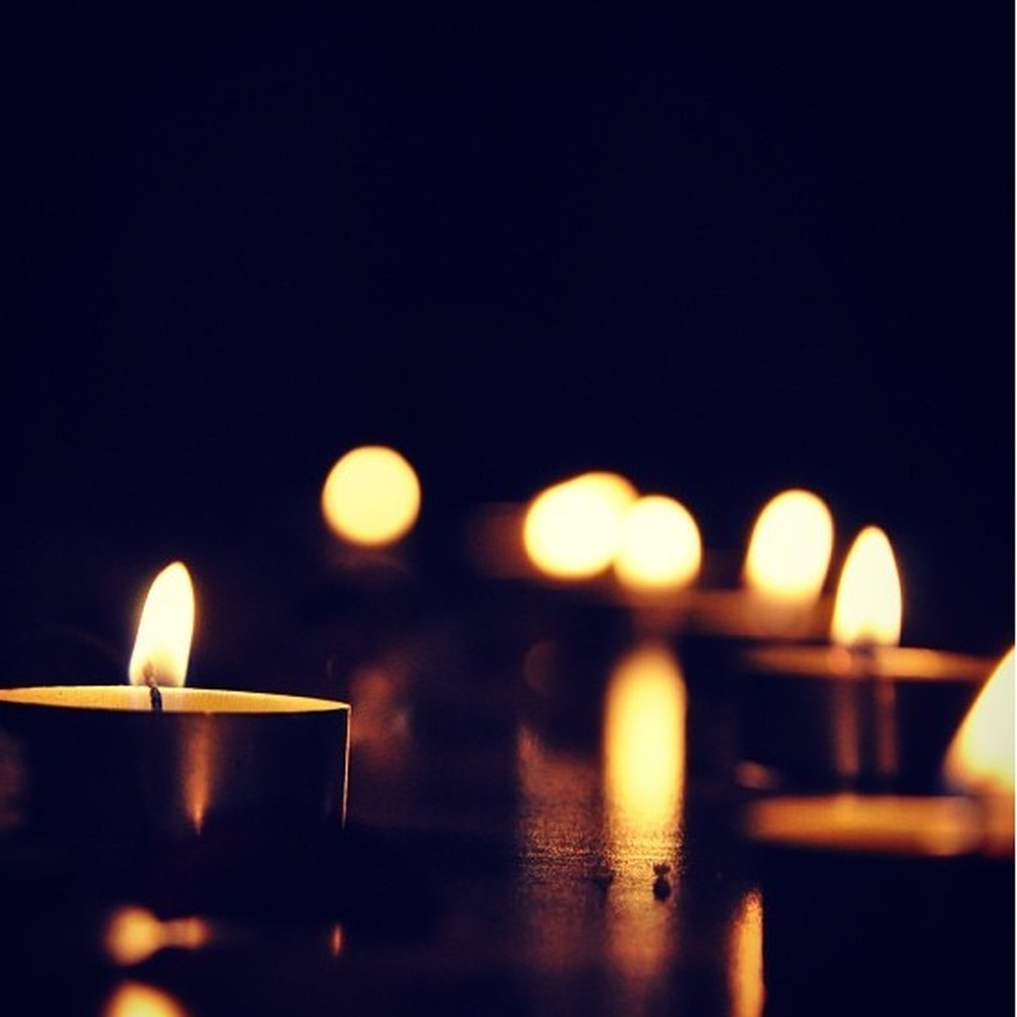 flame, burning, illuminated, indoors, candle, glowing, lit, heat - temperature, candlelight, table, fire - natural phenomenon, dark, in a row, copy space, close-up, reflection, light - natural phenomenon, still life, night, darkroom