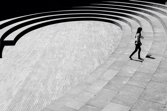 One Person Negative Space Curved Steps Lines Empty Person Walking To The Left Not Recognise Able Urban Space City Shadows High Contrast Patterns Alone Single Empty Lost Lonely Abandoned Walking Light And Dark Black And White