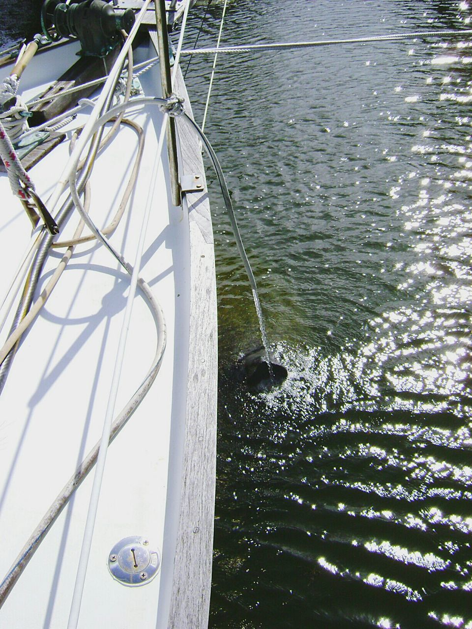 Water Falling From Pipe In Sea From Moored Boat