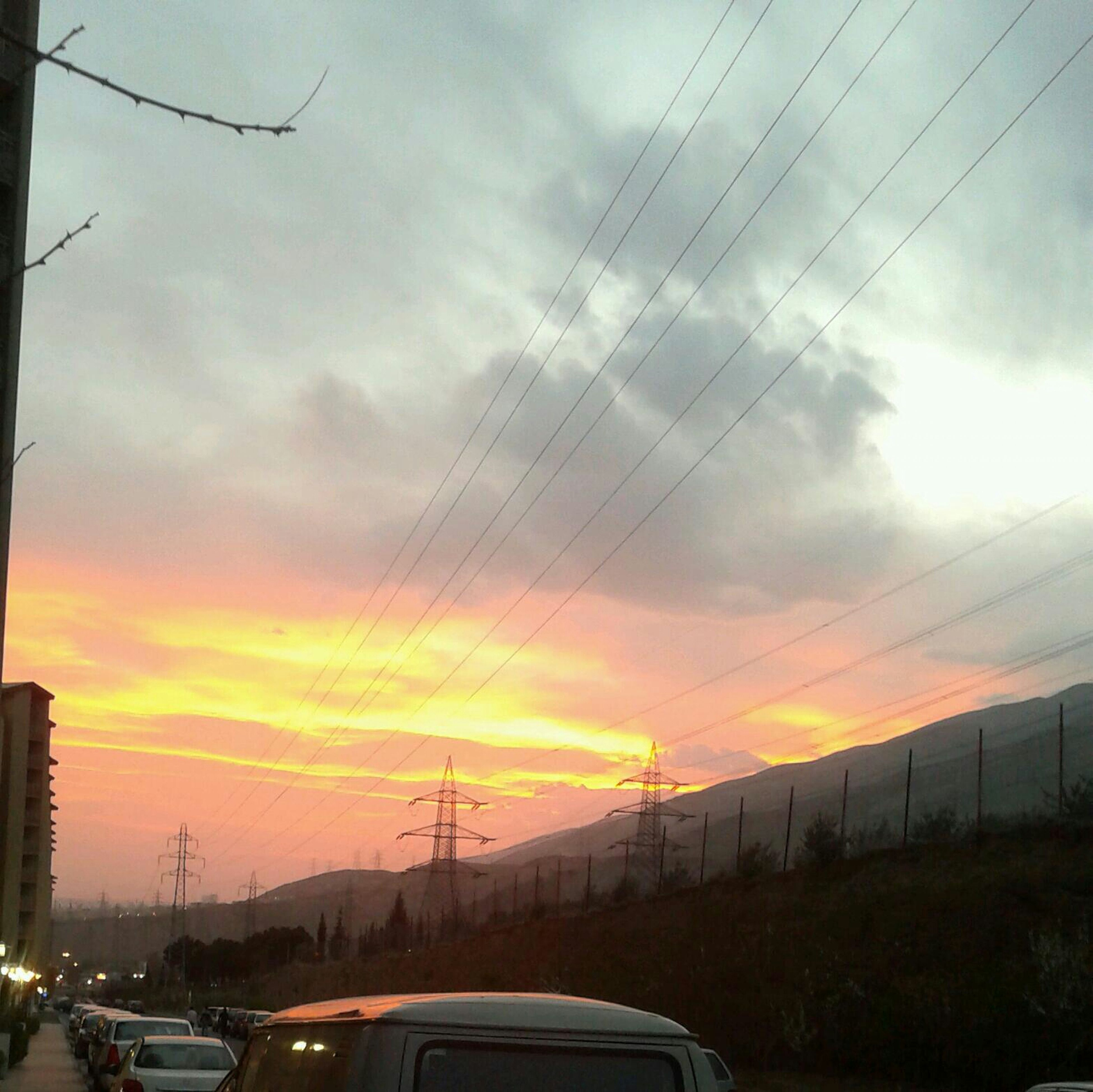 transportation, car, land vehicle, sunset, mode of transport, sky, road, cloud - sky, electricity pylon, power line, orange color, street, silhouette, cloudy, on the move, cloud, connection, dramatic sky, travel, cable
