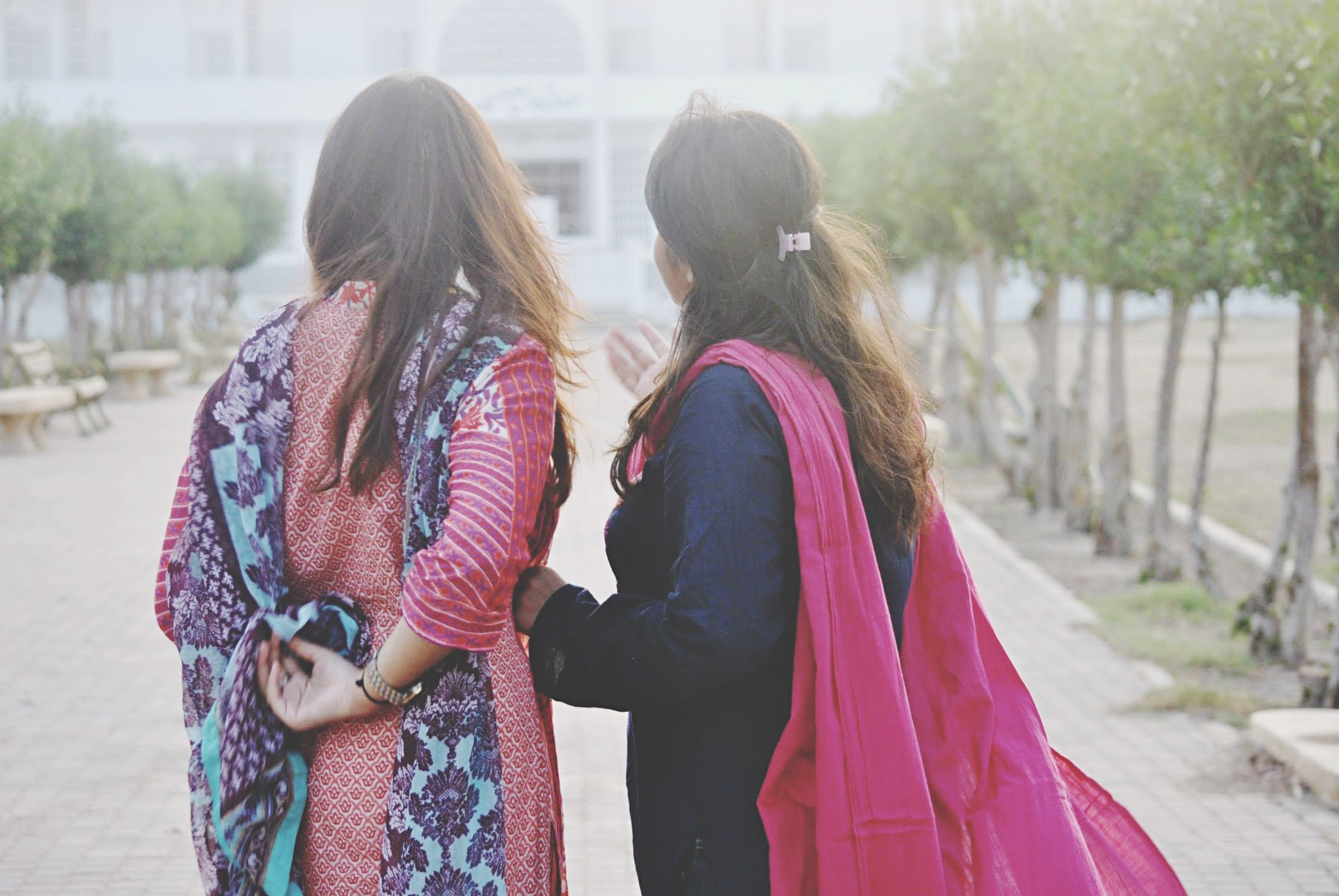 lifestyles, focus on foreground, leisure activity, rear view, person, casual clothing, traditional clothing, waist up, young women, incidental people, standing, day, long hair, outdoors, street, warm clothing, young adult
