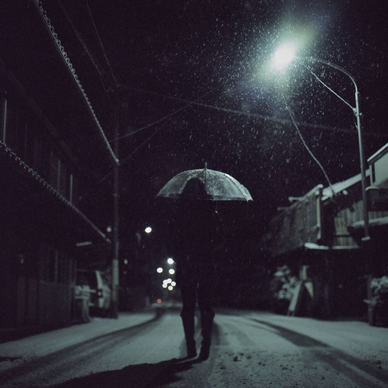 Full Length Rear View Of Woman With Umbrella Walking On Street At Night