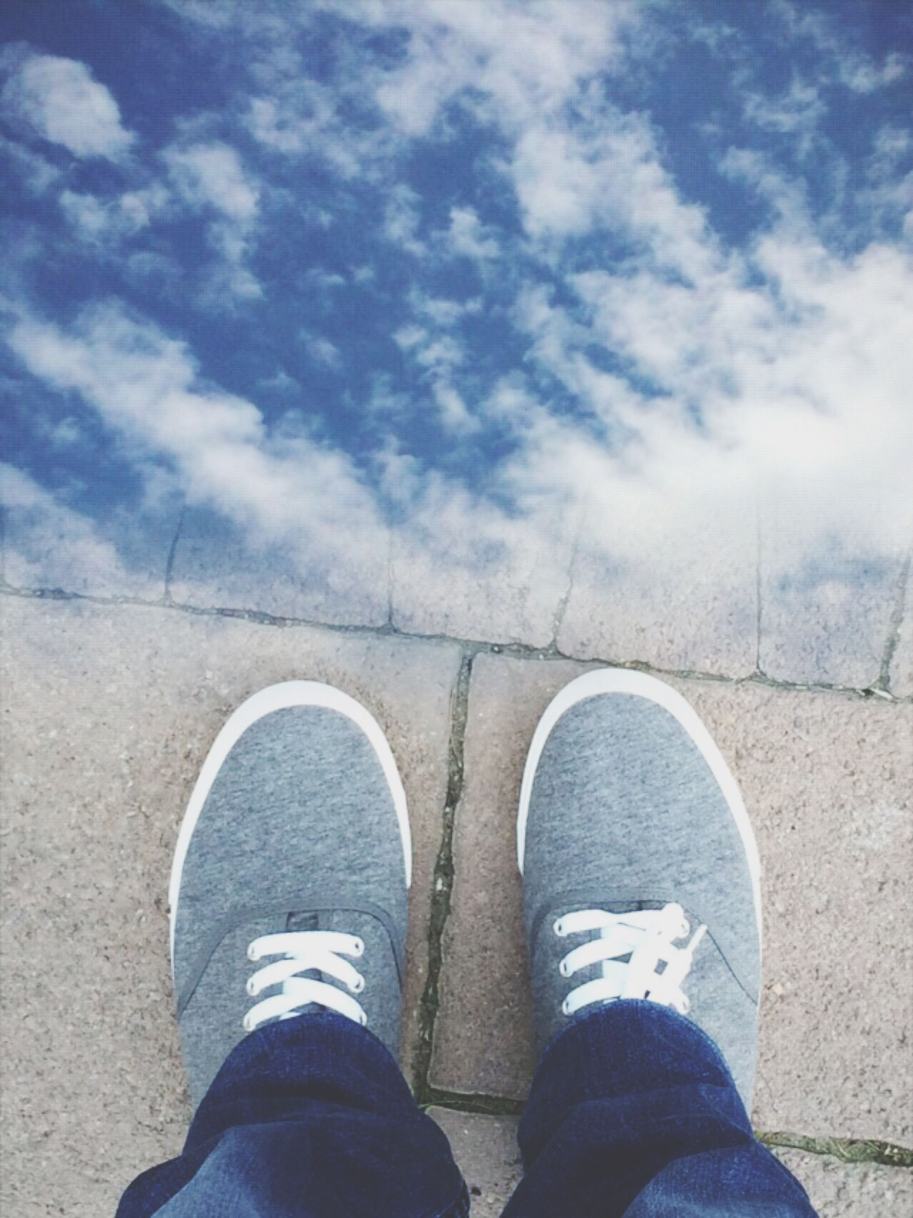 low section, person, shoe, personal perspective, standing, lifestyles, men, human foot, jeans, leisure activity, footwear, sky, unrecognizable person, cloud - sky, day, high angle view, outdoors