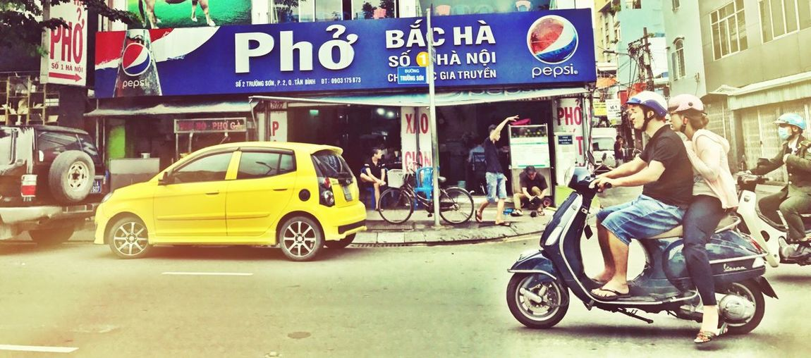 Street City Mode Of Transport Outdoors Land Vehicle Building Exterior Store Built Structure Women Architecture Waiting Game Day Vespa Ho Chi Minh City IPhoneography Early Sunday Morning Vietnam IPhone 7 From A Moving Vehicle From The Car Window Bikers Streetphotography Urbanphotography Transportation View From Where I Sit Mobility In Mega Cities