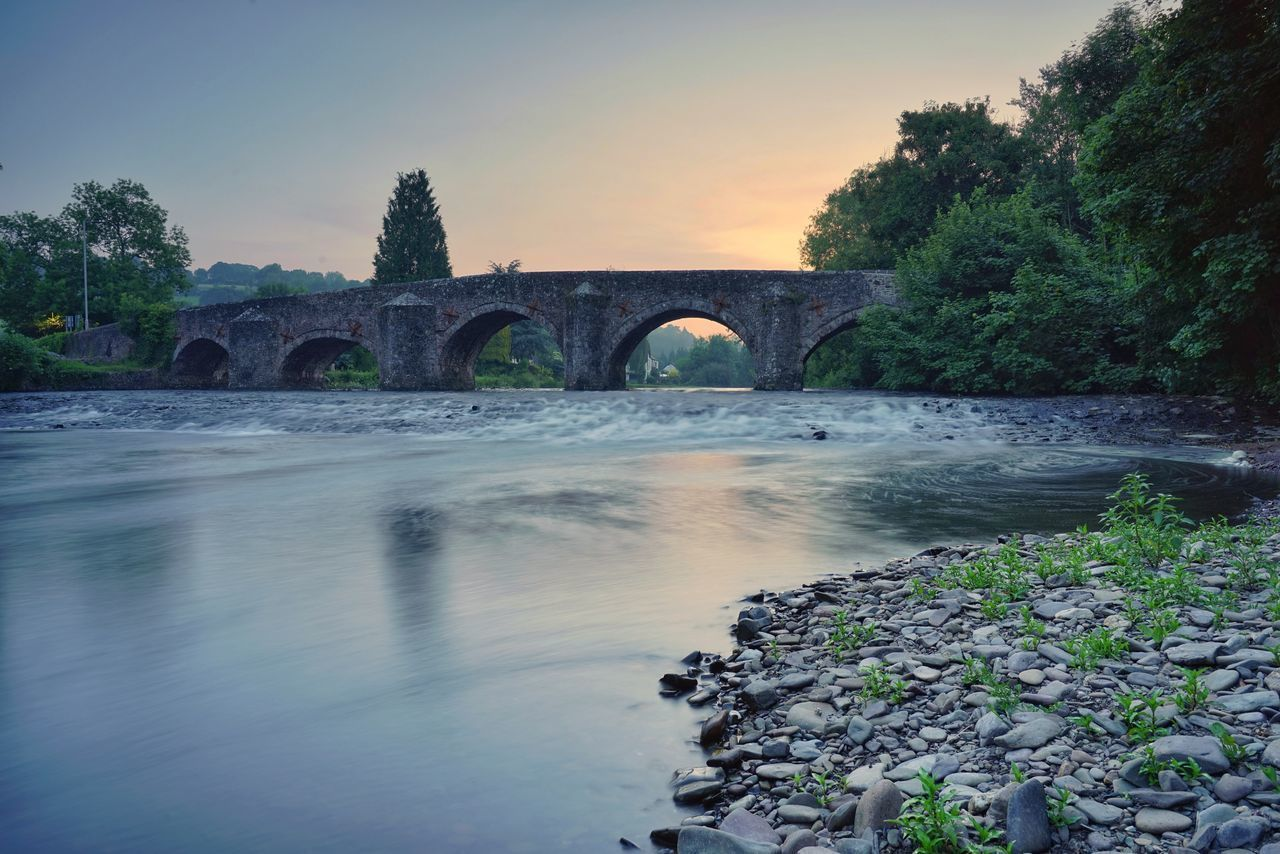 water, bridge - man made structure, nature, connection, river, beauty in nature, sunset, arch, no people, scenics, outdoors, tranquility, tree, built structure, sky, growth, architecture, day