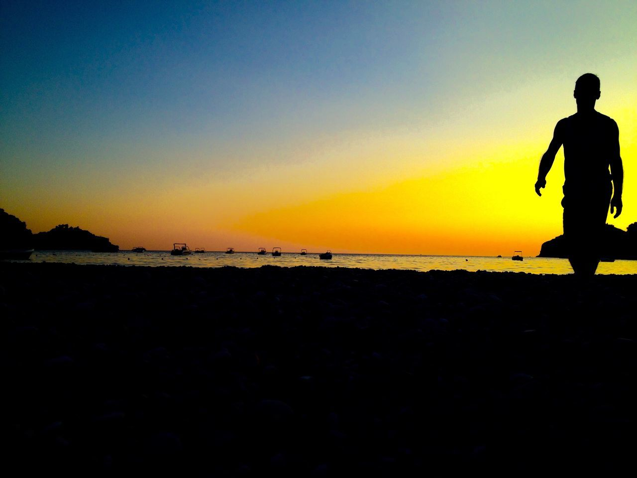 sunset, silhouette, nature, beauty in nature, scenics, beach, tranquil scene, tranquility, orange color, outdoors, one person, real people, sky, full length, sea, lifestyles, water, leisure activity, vacations, clear sky, men, people