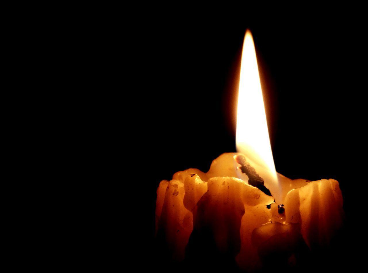 Candle Burning Against Black Background