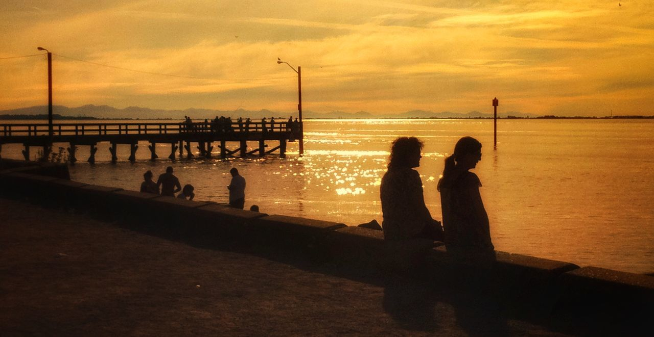 Sunset Silhouette Sea Real People Sky Water Cloud - Sky Two People Men Togetherness Standing Outdoors People Bridge - Man Made Structure Beauty In Nature Nature Adults Only Adult Only Men Day Orange Color Multi Colored Silhouette Beauty In Nature Idyllic