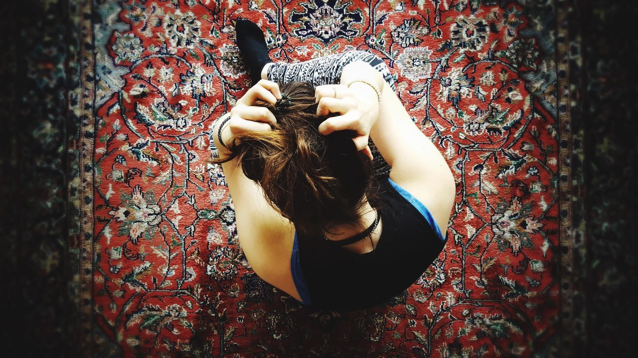 Directly Above Shot Of Woman Sitting With Hands In Hair On Patterned Carpet
