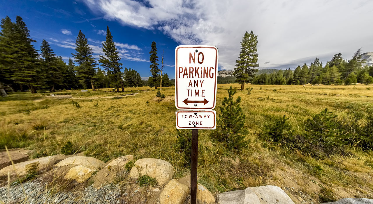 Panoramic landscape view yosemite national park with no parking sign Beauty In Nature Cloud - Sky Day Grass Guidance Landscape Mountain Nature No Parking Sign No People Outdoors Road Sign Scenics Sky Text Tranquility Tree Western Script Yosemite National Park