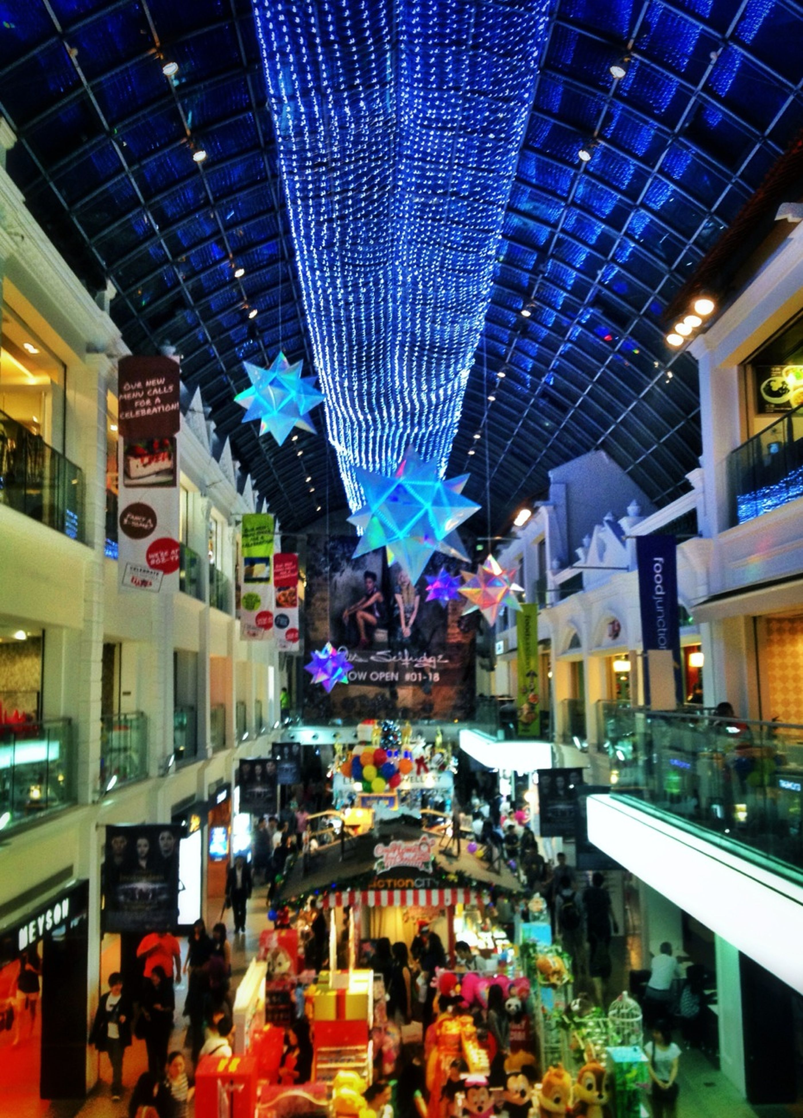 illuminated, architecture, built structure, building exterior, city, large group of people, city life, store, lighting equipment, night, men, person, incidental people, retail, shopping mall, crowd, market, shopping, indoors