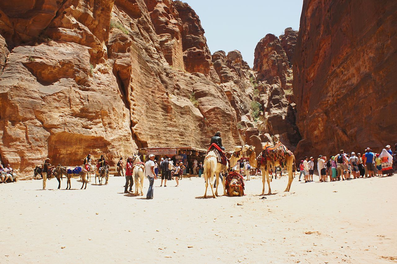 large group of people, rock - object, domestic animals, rock formation, real people, nature, leisure activity, travel destinations, lifestyles, men, desert, vacations, arid climate, adventure, outdoors, sand, sky, day, beauty in nature, women, mammal, ancient civilization, adult, people