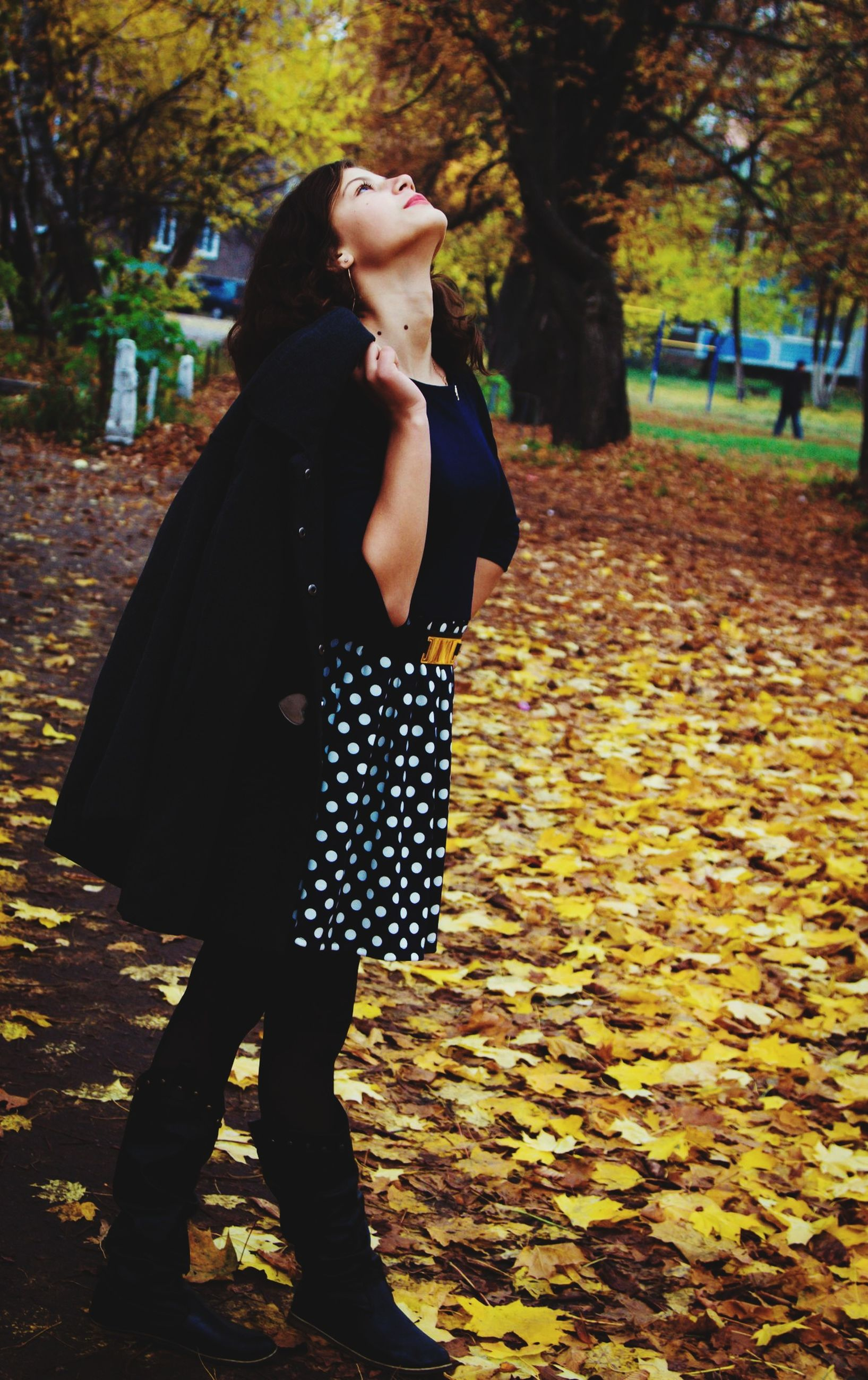 lifestyles, tree, casual clothing, leisure activity, young adult, standing, person, full length, young women, front view, focus on foreground, park - man made space, holding, outdoors, autumn, day, street, side view
