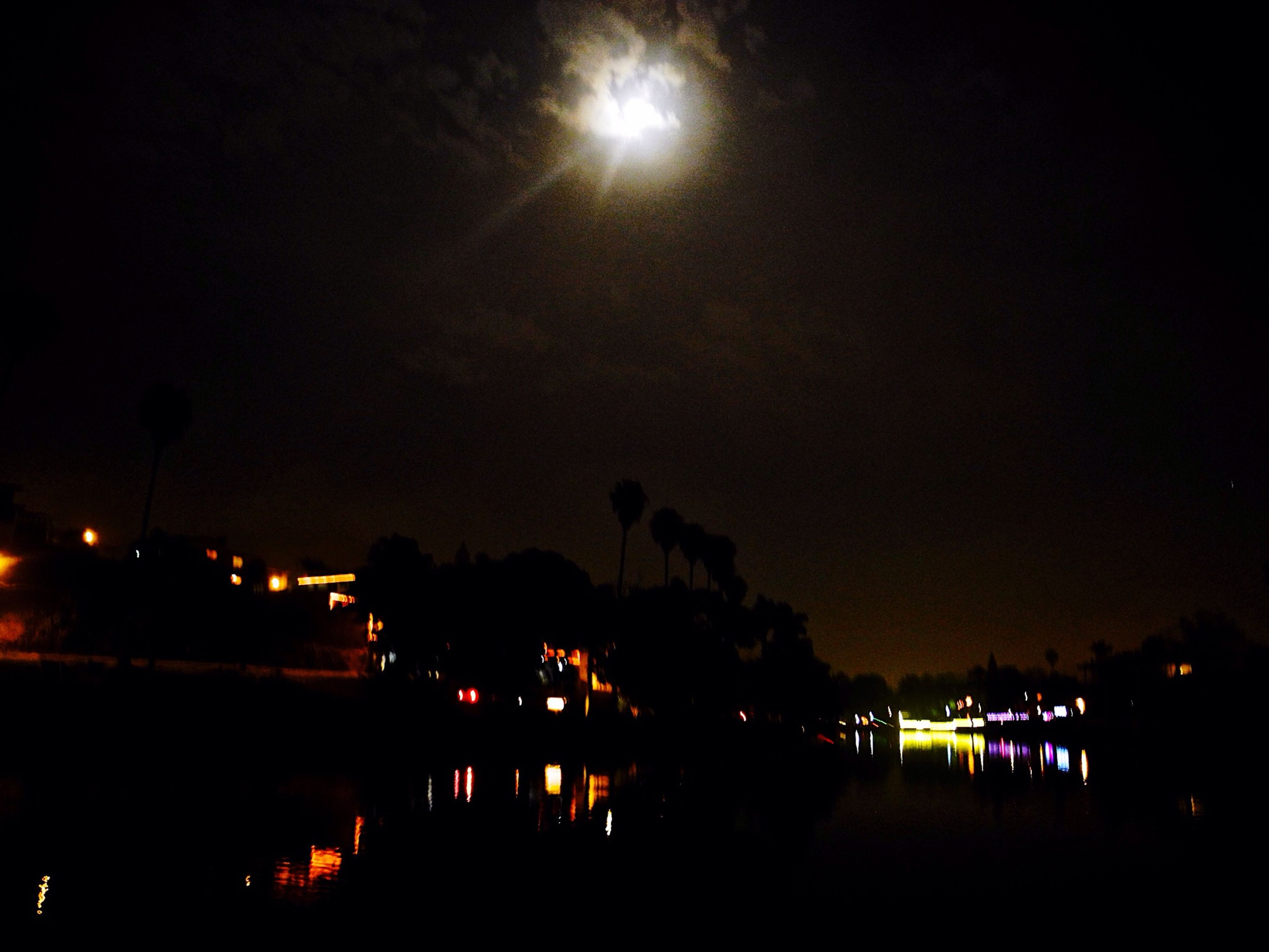 night, illuminated, water, sky, reflection, dark, moon, silhouette, tranquility, glowing, scenics, light - natural phenomenon, tranquil scene, lighting equipment, light, tree, nature, river, waterfront, beauty in nature