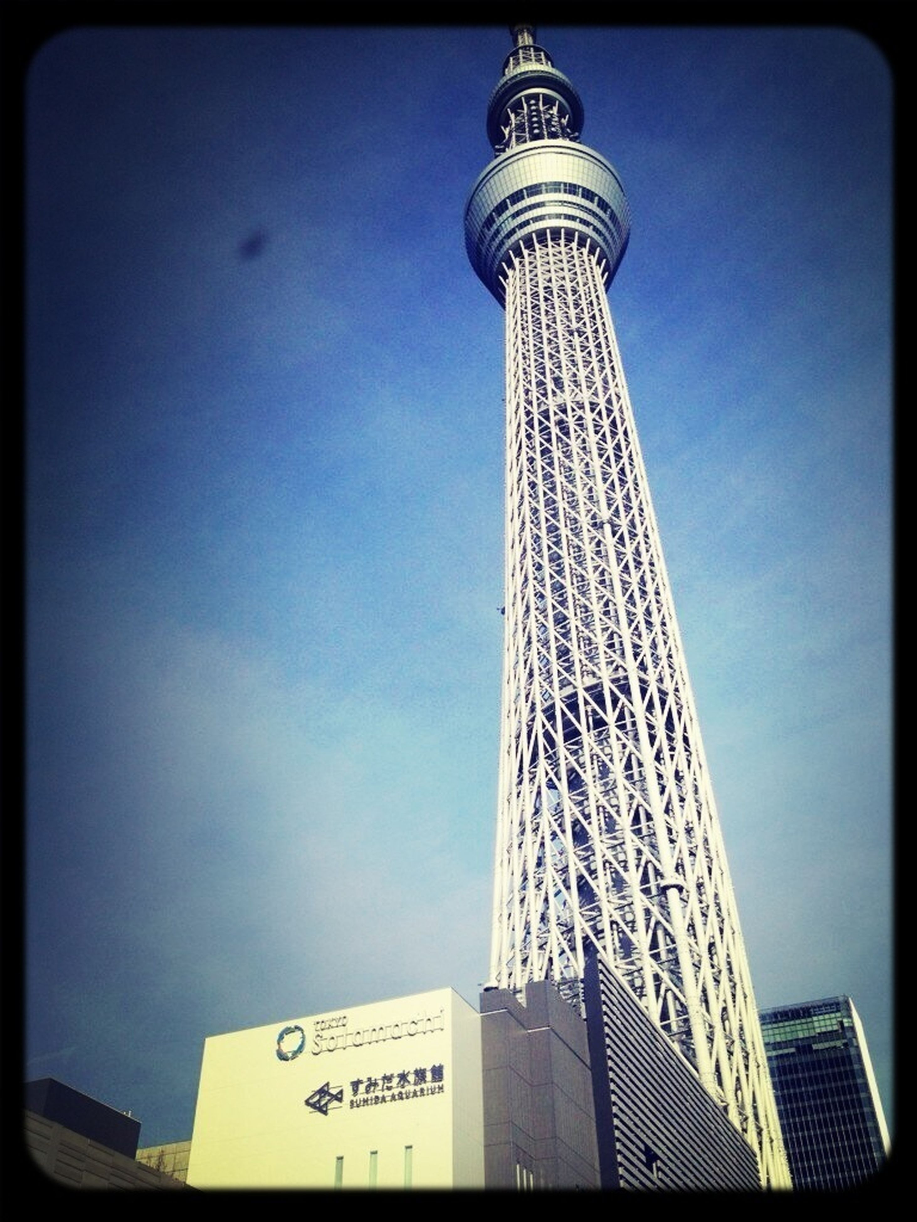 tower, transfer print, built structure, architecture, low angle view, tall - high, communication, international landmark, building exterior, auto post production filter, communications tower, travel destinations, famous place, clear sky, capital cities, sky, tourism, blue, travel, tall