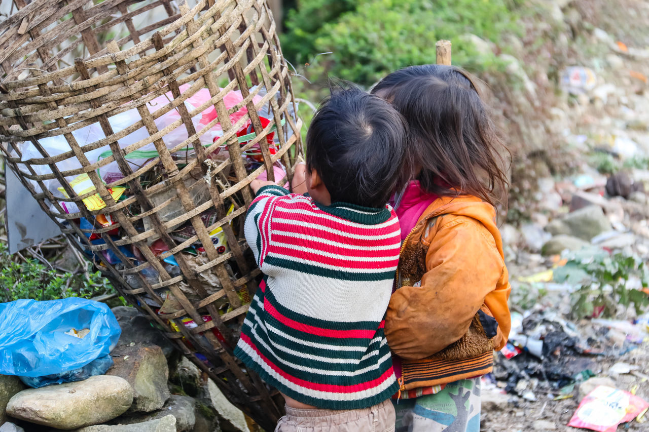Children with a pile of garbage Adult Casual Clothing Childhood Day Outdoors People Real People Rear View Two People