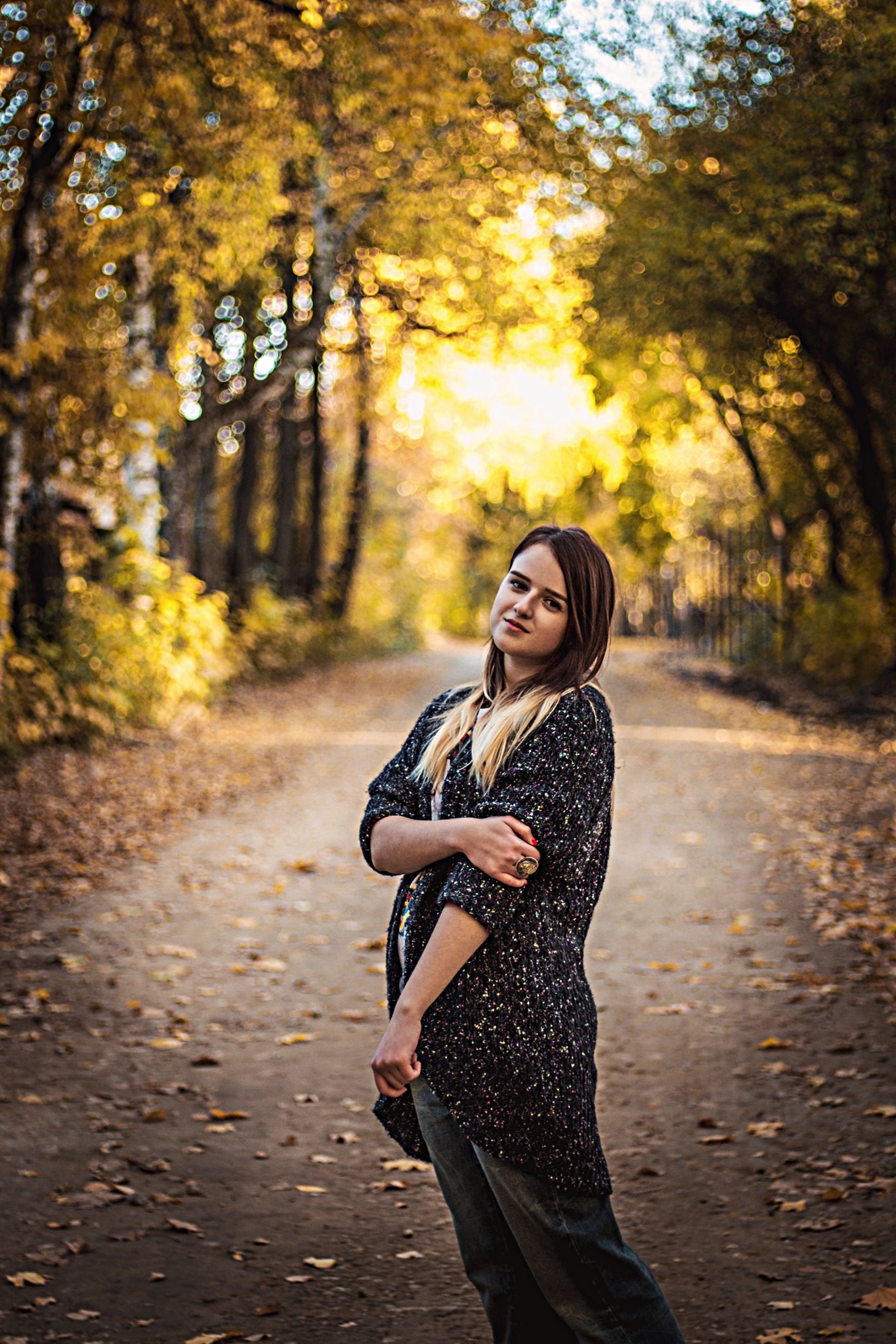tree, lifestyles, young adult, leisure activity, road, transportation, casual clothing, young women, focus on foreground, person, front view, full length, forest, street, outdoors, sunlight, holding, standing