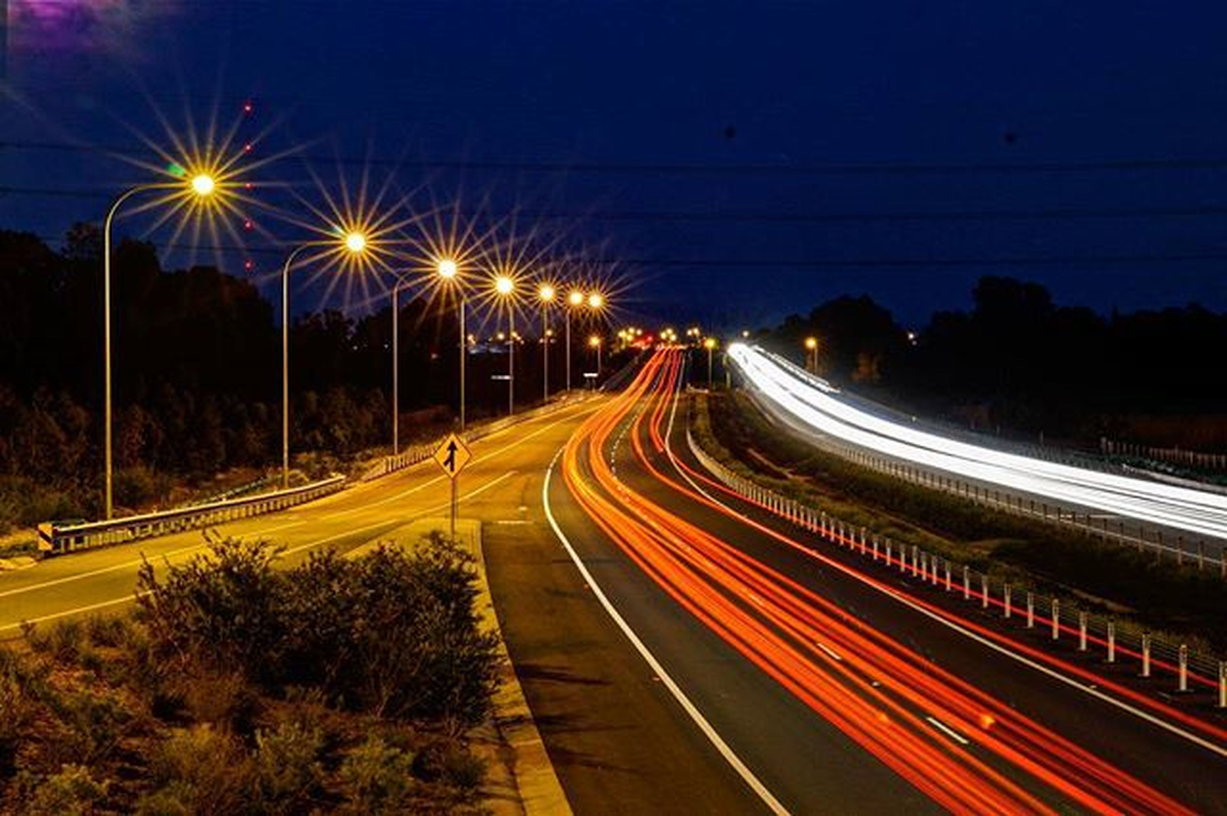 illuminated, light trail, long exposure, night, transportation, speed, motion, blurred motion, road, traffic, street light, city, high angle view, street, highway, on the move, railroad track, sky, the way forward, tail light