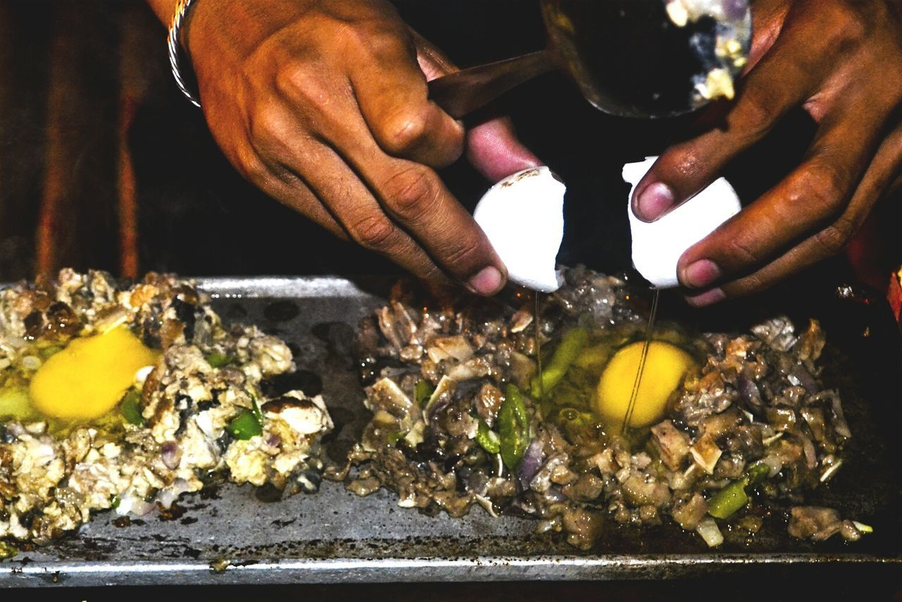 Close-Up Of Cropped Hand Preparing Sizzling Sisig